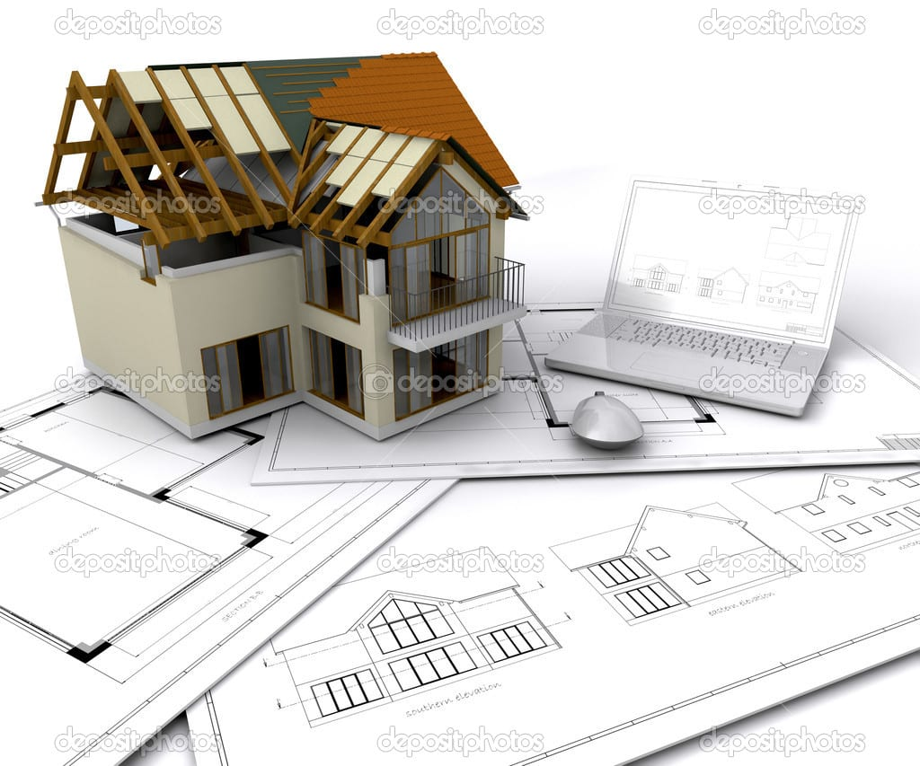 House under construction on plans with laptop